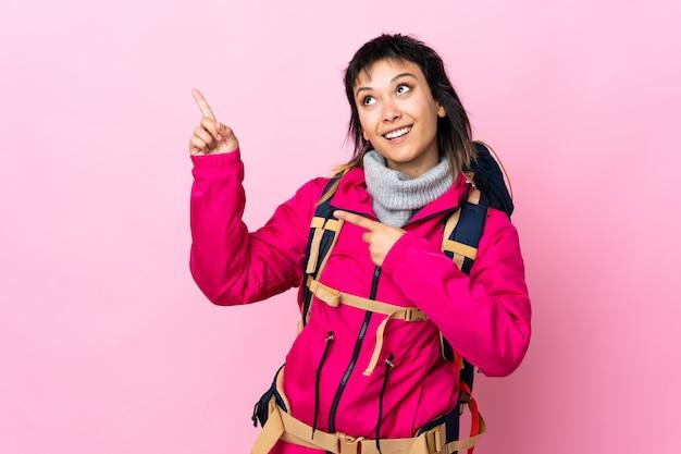 Młoda alpinistka z dużym plecakiem nad odizolowanym różowym palcem wskazującym to świetny pomysł