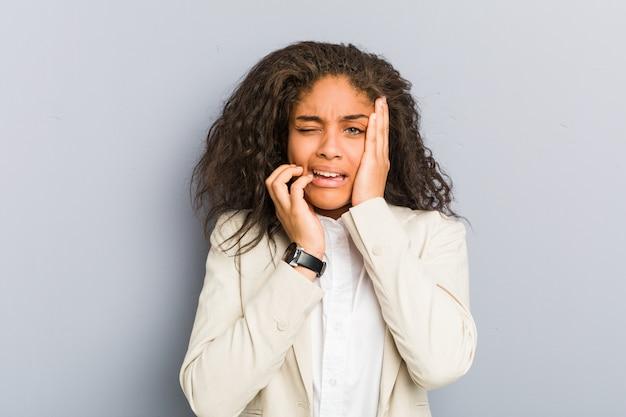 Młoda amerykanin afrykańskiego pochodzenia biznesowa kobieta jęczy dyskretnie i płacze.