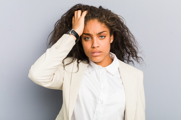 Młoda amerykanin afrykańskiego pochodzenia biznesowa kobieta męczył i bardzo śpiący utrzymuje rękę na głowie.