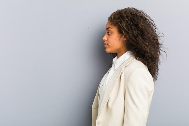 Młoda amerykanin afrykańskiego pochodzenia biznesowa kobieta ono przygląda się z lewej strony, z ukosa poza.