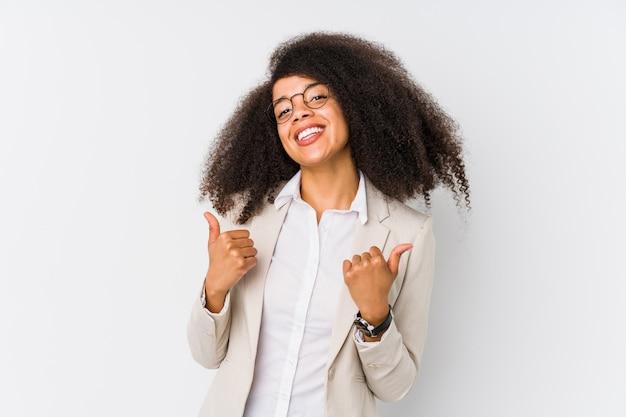 Młoda amerykanin afrykańskiego pochodzenia biznesowa kobieta podnosi oba aprobaty, uśmiechnięty i ufny.
