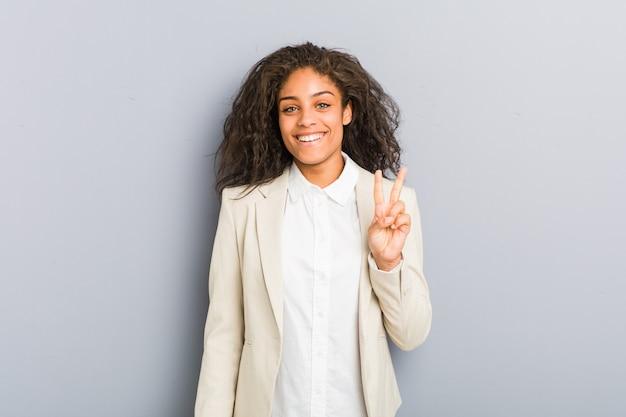 Młoda amerykanin afrykańskiego pochodzenia biznesowa kobieta pokazuje zwycięstwo znaka i ono uśmiecha się szeroko.