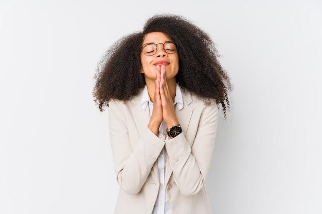 Młoda amerykanin afrykańskiego pochodzenia biznesowa kobieta trzyma ręki w modli się blisko usta, czuje ufnego.