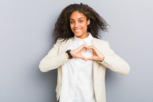 Młoda amerykanin afrykańskiego pochodzenia biznesowa kobieta uśmiecha się kierowego kształt z rękami i pokazuje.