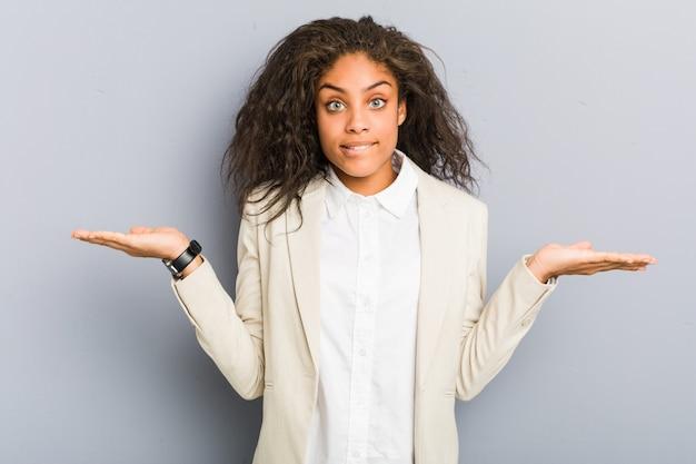 Młoda amerykanin afrykańskiego pochodzenia biznesowa kobieta wprawiać w zakłopotanie i wątpliwie wzrusza ramionami ramiona trzymać kopię.