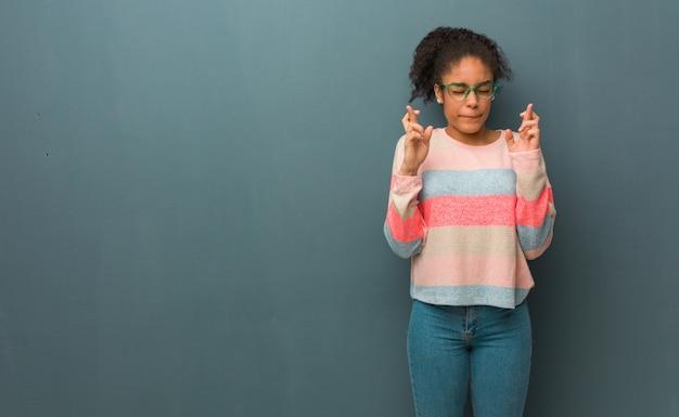 Młoda amerykanin afrykańskiego pochodzenia dziewczyna krzyżuje palce za mieć szczęście z niebieskimi oczami