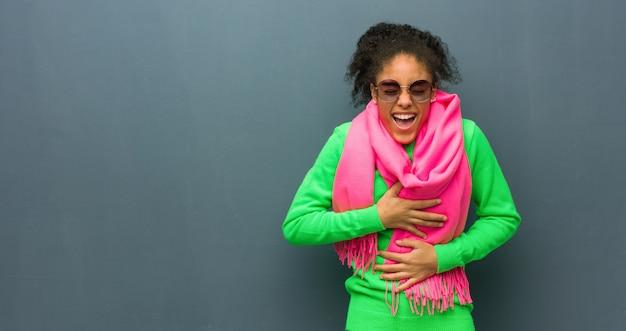 Młoda amerykanin afrykańskiego pochodzenia dziewczyna śmia się i ma zabawę z niebieskimi oczami