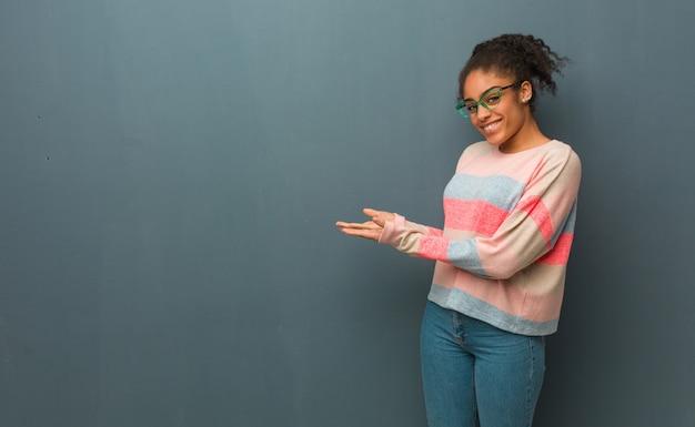Młoda amerykanin afrykańskiego pochodzenia dziewczyna trzyma coś z rękami z niebieskimi oczami