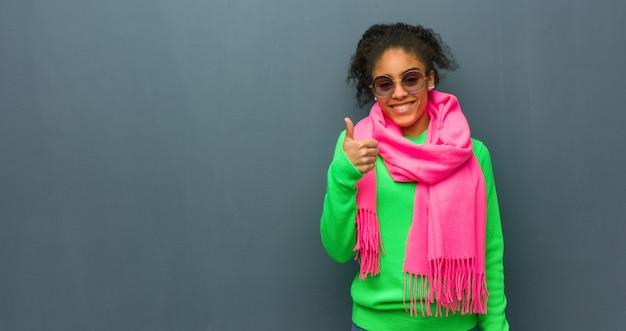 Młoda amerykanin afrykańskiego pochodzenia dziewczyna uśmiecha się kciuk up i podnosi niebieskie oczy