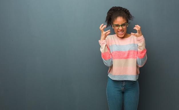 Młoda amerykanin afrykańskiego pochodzenia dziewczyna z niebieskimi oczami gniewnymi i zdenerwowanymi