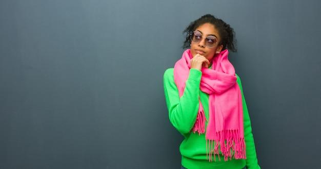 Młoda amerykanin afrykańskiego pochodzenia dziewczyna z niebieskimi oczami myśleć o pomysle