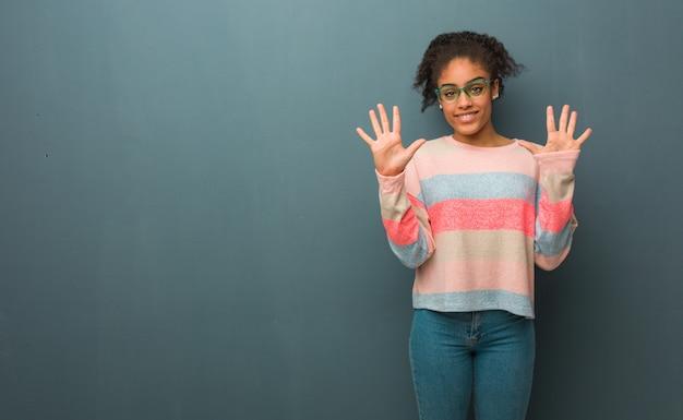 Młoda amerykanin afrykańskiego pochodzenia dziewczyna z niebieskimi oczami pokazuje liczbę dziesięć