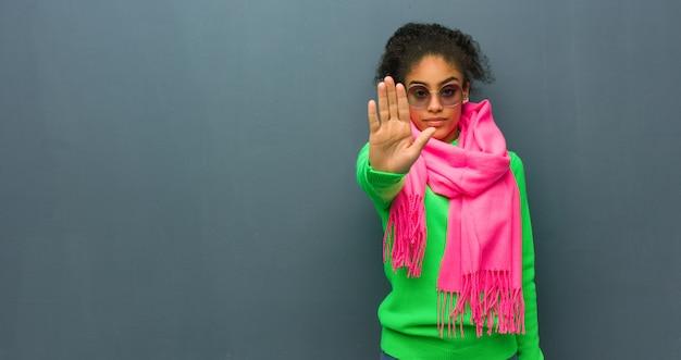 Młoda amerykanin afrykańskiego pochodzenia dziewczyna z niebieskimi oczami stawia rękę w przód