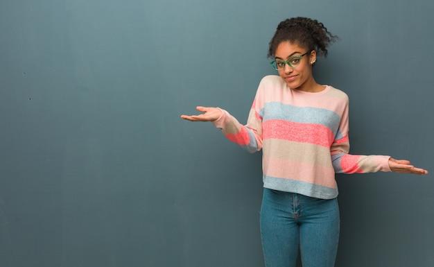 Młoda amerykanin afrykańskiego pochodzenia dziewczyna z niebieskimi oczami wątpi i wzrusza ramionami ramiona