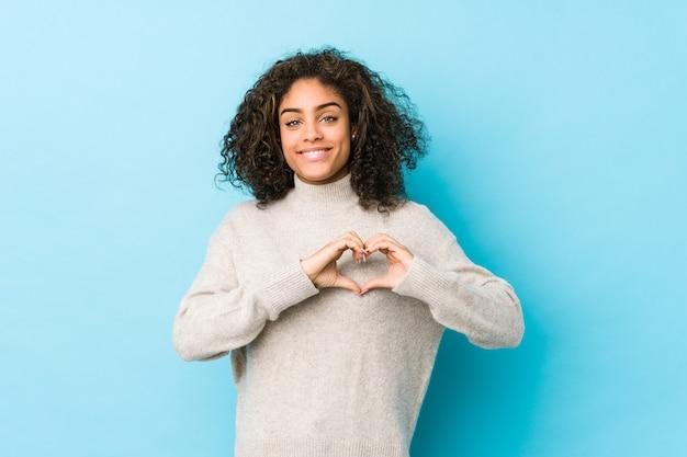 Młoda amerykanin afrykańskiego pochodzenia kędzierzawego włosy kobieta uśmiecha się kierowego kształt z rękami i pokazuje.