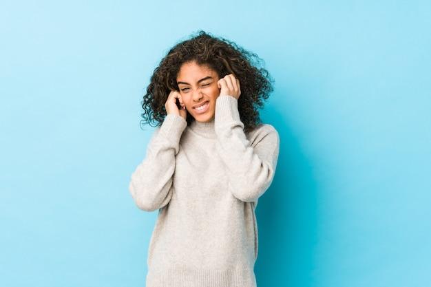 Młoda amerykanin afrykańskiego pochodzenia kędzierzawego włosy kobieta zakrywa ucho z rękami.