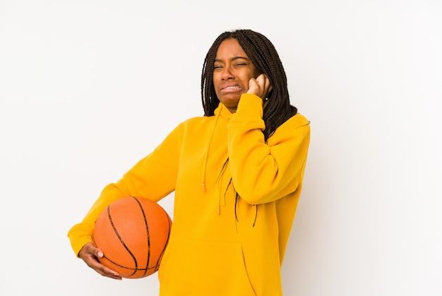 Młoda amerykanin afrykańskiego pochodzenia kobieta bawić się koszykówkę odizolowywał nakrywkowych ucho z rękami.