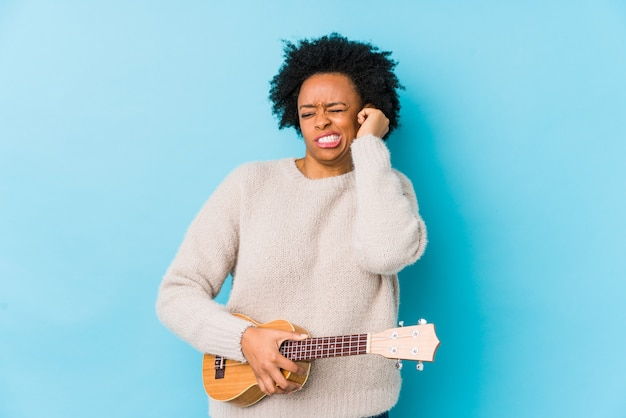 Młoda amerykanin afrykańskiego pochodzenia kobieta bawić się ukelele nakrywkowych ucho z rękami.