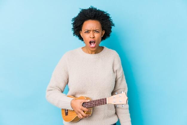 Młoda amerykanin afrykańskiego pochodzenia kobieta bawić się ukelele odizolowywał krzyczeć bardzo gniewnego i agresywnego.