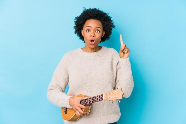 Młoda amerykanin afrykańskiego pochodzenia kobieta bawić się ukelele odizolowywał mieć niektóre doskonałego pomysł, pojęcie twórczość.