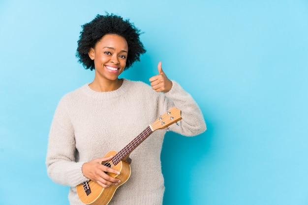 Młoda amerykanin afrykańskiego pochodzenia kobieta bawić się ukelele odizolowywał uśmiecha się kciuk up i podnosi