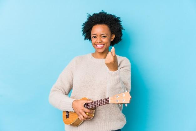 Młoda amerykanin afrykańskiego pochodzenia kobieta bawić się ukelele odizolowywał wskazywać z palcem przy tobą tak jakby zapraszający zbliżał się.