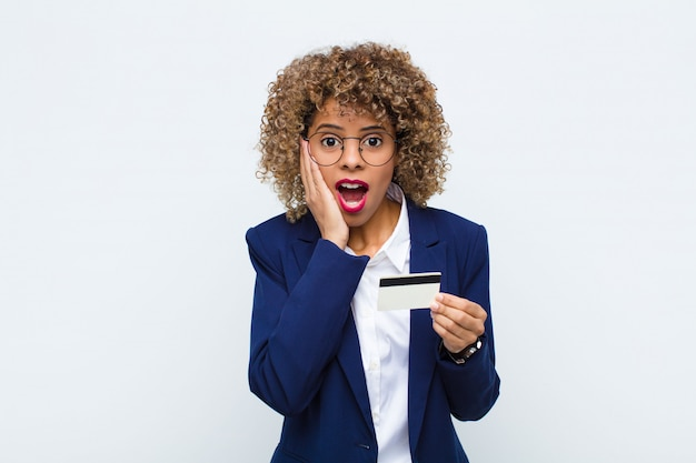 Młoda amerykanin afrykańskiego pochodzenia kobieta czuje się szczęśliwa, podekscytowana i zaskoczona, patrząc z boku obiema rękami na twarzy za pomocą karty kredytowej