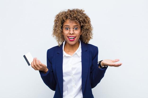 Młoda amerykanin afrykańskiego pochodzenia kobieta czuje się zdziwiona i zmieszana, wątpiąc, ważąc lub wybierając różne opcje z zabawnym wyrazem karty kredytowej