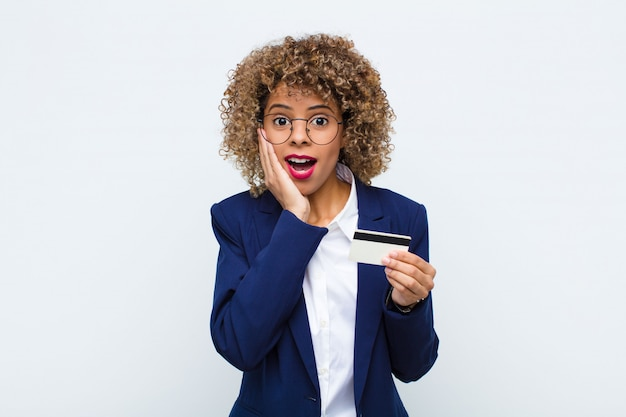 Młoda amerykanin afrykańskiego pochodzenia kobieta czuje się zszokowana i przestraszona, wygląda przerażona z otwartymi ustami i rękami na policzkach z kartą kredytową