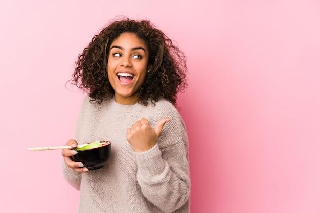 Młoda amerykanin afrykańskiego pochodzenia kobieta je kluski punkty z kciuka palcem daleko od, śmia się i beztroskiego.