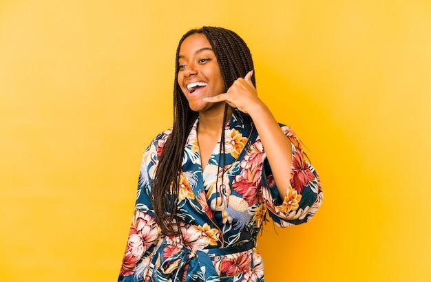 Młoda amerykanin afrykańskiego pochodzenia kobieta jest ubranym azjatykcie pijama odizolowywa pokazywać gesta telefonu komórkowego gesta palcami.