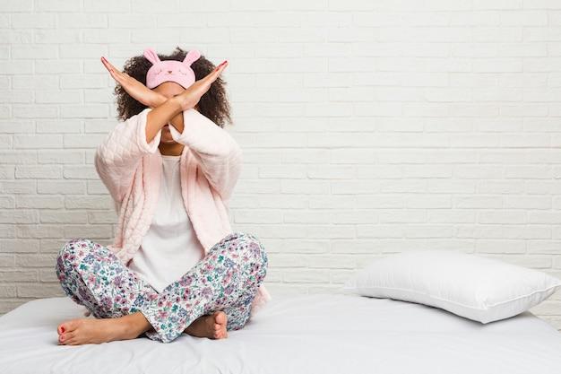Młoda amerykanin afrykańskiego pochodzenia kobieta jest ubranym pijama w łóżku jest ubranym dwa ręki krzyżujący, zaprzeczenia pojęcie.