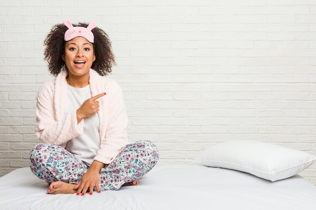 Młoda amerykanin afrykańskiego pochodzenia kobieta jest ubranym pijama w łóżku jest ubranym pijama ono uśmiecha się i wskazuje na boku, pokazuje coś przy pustą przestrzenią.