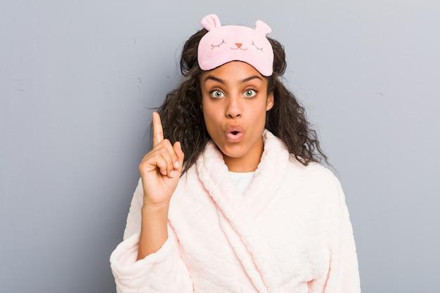 Młoda amerykanin afrykańskiego pochodzenia kobieta jest ubranym piżamę i sen maskę ma niektóre doskonałego pomysł, pojęcie twórczość.