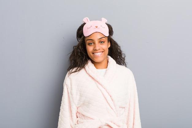 Młoda amerykanin afrykańskiego pochodzenia kobieta jest ubranym piżamę i sen maskę szczęśliwą, uśmiechniętą i wesołą.
