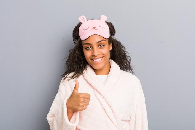 Młoda amerykanin afrykańskiego pochodzenia kobieta jest ubranym piżamę i sen maskę uśmiecha się kciuk up i podnosi