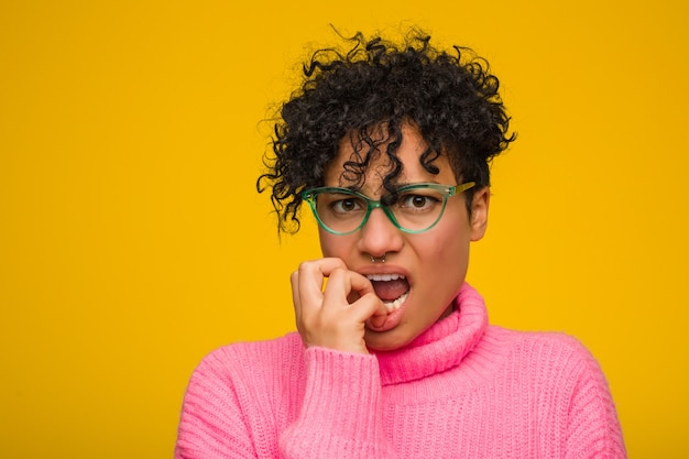 Młoda amerykanin afrykańskiego pochodzenia kobieta jest ubranym różowego pulower obgryzający paznokcie, nerwowa i bardzo niespokojna.