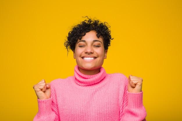 Młoda amerykanin afrykańskiego pochodzenia kobieta jest ubranym różowego pulower podnosi pięść, czuje się szczęśliwy i pomyślny. koncepcja zwycięstwa.