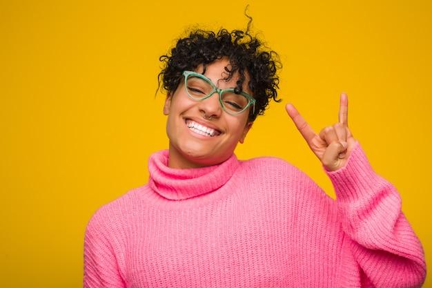 Młoda amerykanin afrykańskiego pochodzenia kobieta jest ubranym różowego pulower pokazuje rogi gest jako rewoluci pojęcie.