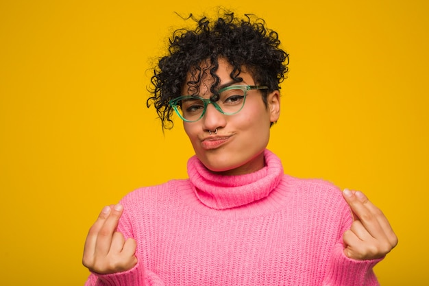 Młoda amerykanin afrykańskiego pochodzenia kobieta jest ubranym różowego pulower pokazuje, że nie ma pieniędzy.