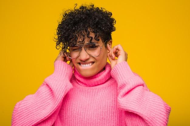 Młoda amerykanin afrykańskiego pochodzenia kobieta jest ubranym różowego pulower zakrywa ucho z rękami.