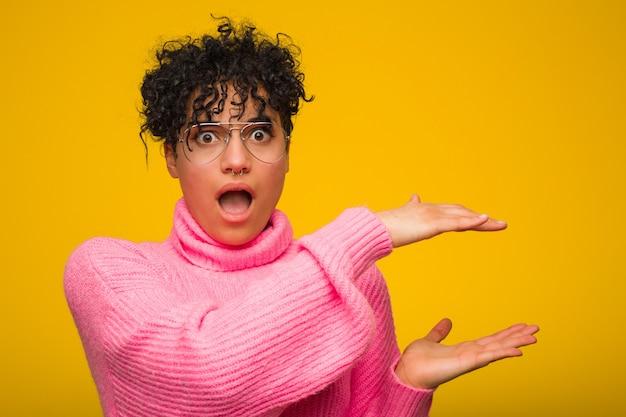 Młoda amerykanin afrykańskiego pochodzenia kobieta jest ubranym różowego pulower zszokowanego i zadziwiającego trzymający odbitkową przestrzeń między rękami.