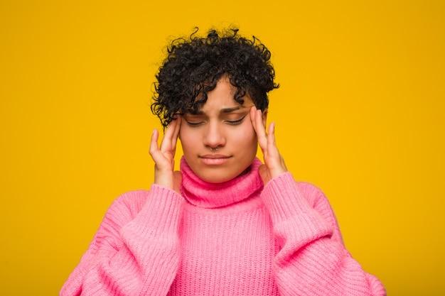 Młoda amerykanin afrykańskiego pochodzenia kobieta jest ubranym różowego sweter dotyka świątynie i ma ból głowy.