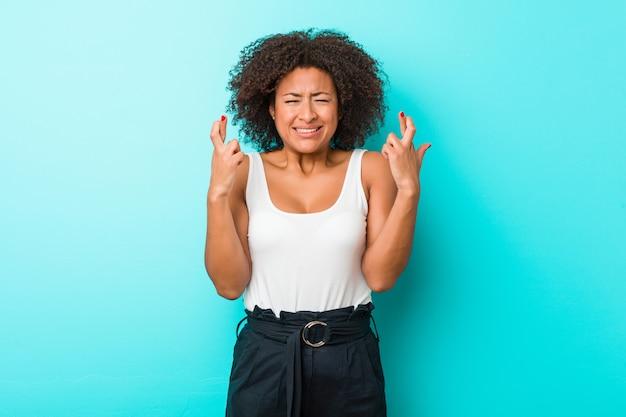 Młoda amerykanin afrykańskiego pochodzenia kobieta krzyżuje palce dla mieć szczęście