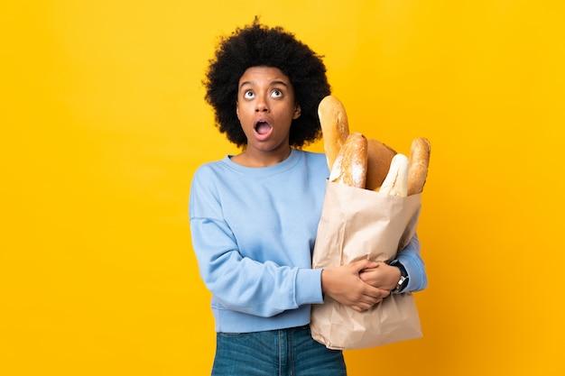 Młoda amerykanin afrykańskiego pochodzenia kobieta kupuje coś chleb na kolor żółty ściany przyglądającym up z zdziwionym wyrażeniem