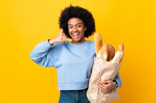 Młoda amerykanin afrykańskiego pochodzenia kobieta kupuje coś chleb na żółtej ścianie robi telefonu gestowi. oddzwoń do mnie znak