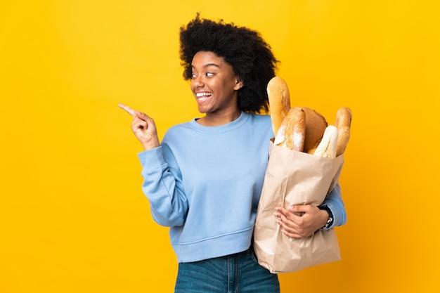 Młoda amerykanin afrykańskiego pochodzenia kobieta kupuje coś chleb na żółtej ścianie zamierza realizować rozwiązanie podczas gdy podnoszący palec w górę