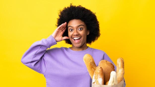 Młoda amerykanin afrykańskiego pochodzenia kobieta kupuje coś chleb odizolowywającego na żółtym tle z niespodzianki wyrażeniem