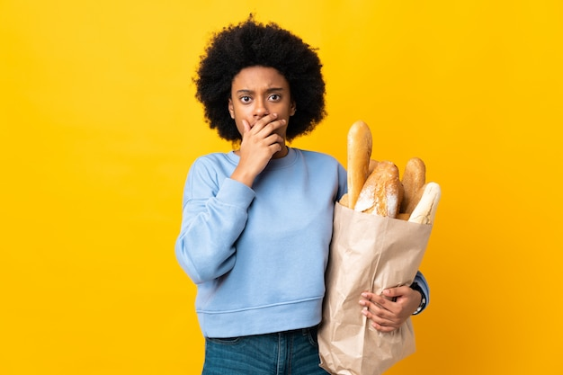 Młoda amerykanin afrykańskiego pochodzenia kobieta kupuje coś chleb odizolowywającego na żółtym tle zaskakującym i szokującym podczas gdy patrzejący dobrze