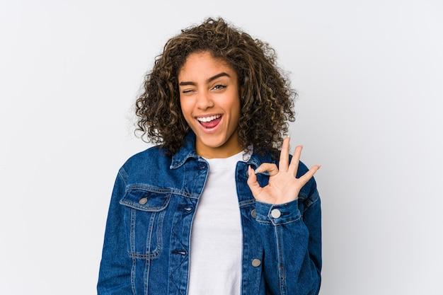 Młoda amerykanin afrykańskiego pochodzenia kobieta mruga oko i trzyma dobrze gest ręką.